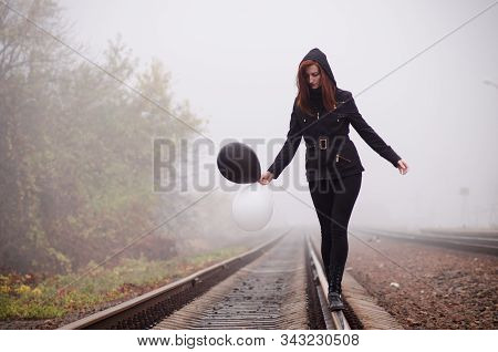 Lonely girl in black clothing walking on the rails in a fog. She holds a black and white balloon in her hand and it fly away. Concept of choice, target, good and evil, way in life stock photo