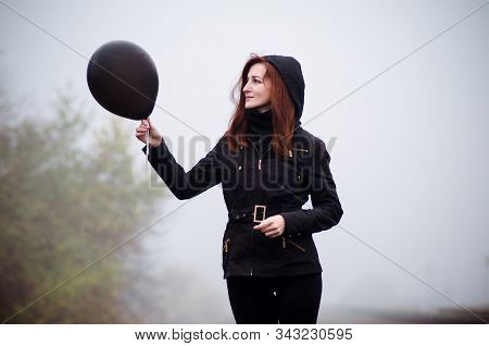 Lonely girl in black clothing walking in a fog. She holds a black balloon in her hand and it fly away. Concept of choice, target, good and evil, way in life stock photo