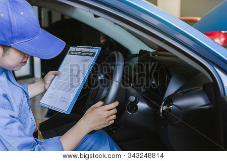 Asian Man mechanic inspection writing note on clipboard.Blue car for service maintenance insurance with car engine.for transport automobile automotive image. stock photo