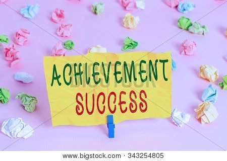 Handwriting text writing Achievement Success. Concept meaning status of having achieved and accomplished an aim Colored crumpled papers empty reminder pink floor background clothespin. stock photo