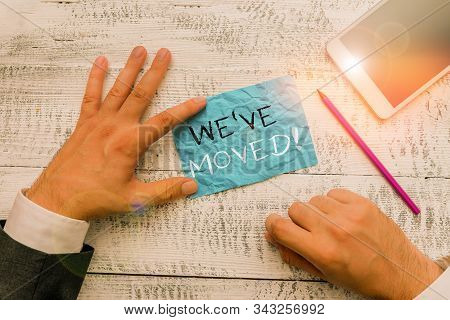 Writing note showing We Ve Moved. Business photo showcasing having strong feelings sadness or sympathy has said or done Hand hold note paper near writing equipment and smartphone. stock photo