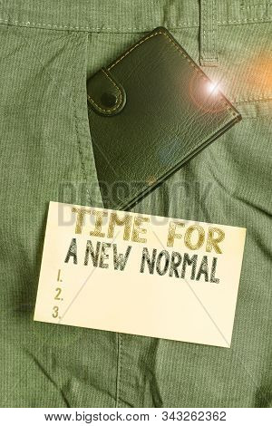 Writing note showing Time For A New Normal. Business photo showcasing Make a big dramatic change Replace the expected Small wallet inside trouser front pocket near notation paper. stock photo