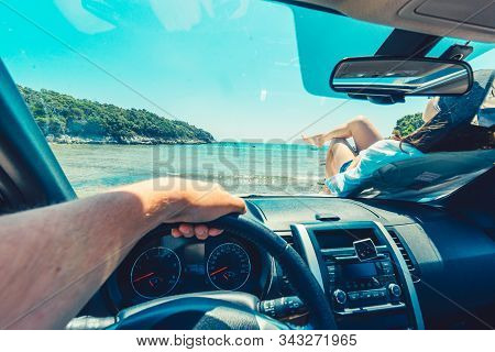 first person view man sitting in car woman laying at hood stock photo