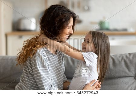 Loving mother embracing pre-school daughter showing her love and care stock photo
