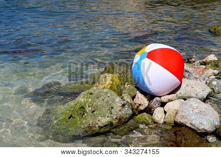 Inflatable beach ball on the rock beach in Italy with sea in the background - summer holiday vacations concept - Italy, Monopoli, Adriatic Sea stock photo
