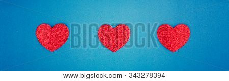 Happy Valentine Day. Beautiful card wallpaper with three red hearts in centre on blue background. Concept of polygamy love and February holiday. Web banner header for website. stock photo