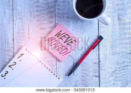 Handwriting text We Ve Moved. Concept meaning having strong feelings sadness or sympathy has said or done Stationary placed next to a cup of black coffee above the wooden table. stock photo