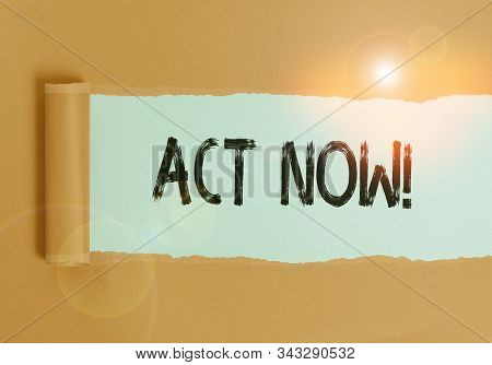Text sign showing Act Now. Conceptual photo fulfil the function or serve the purpose of Take action Do something Cardboard which is torn in the middle placed above a plain table backdrop. stock photo