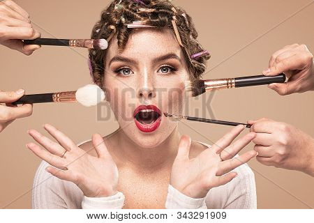 Beautiful woman and professional makeup artists hands with different brushes. Closeup beauty portrait of attractive girl with glamour face. stock photo