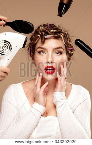 Beautiful woman and professional hairdressers artists hands with different equipment. Closeup beauty portrait of attractive girl with glamour face. stock photo
