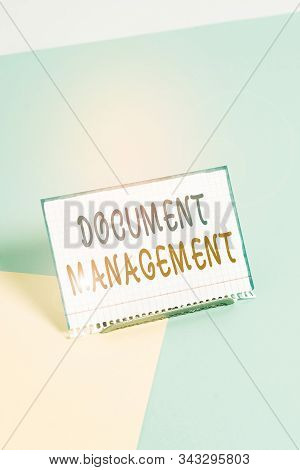 Text sign showing Document Management. Conceptual photo Computerized analysisagement of electronic documents Paper placed tilted above buffer wire on soft pastel multi colours backdrop. stock photo