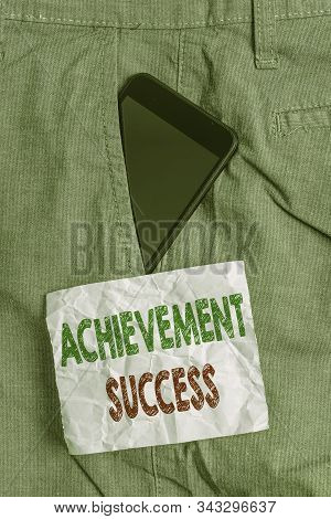 Handwriting text Achievement Success. Concept meaning status of having achieved and accomplished an aim Smartphone device inside formal work trousers front pocket near note paper. stock photo