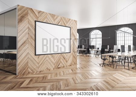 Wooden coworking office interior with computers on table and blank poster on wall. 3D Rendering stock photo