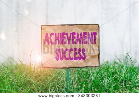 Handwriting text writing Achievement Success. Concept meaning status of having achieved and accomplished an aim Crumpled paper attached to a stick and placed in the green grassy land. stock photo