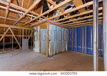 Insulation of attic with insulation material and pipe heating system a building with wooden beams of a roof structure stock photo