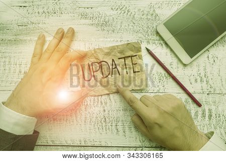 Text sign showing Update. Conceptual photo by adding new information or making corrections Up to date Hand hold note paper near writing equipment and modern smartphone device. stock photo