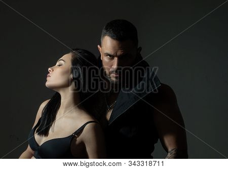 Muscular man. Couple in love on dark background. Relax. Fashion studio photo of beautiful couple. Couple In Love. Young sexy couple. Loving everything about her. Love. Beautiful young lovers stock photo