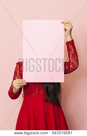Young pretty woman in masquerade mask holding an empty card. 20s middle-eastern female holds blank paper. Advertisement, banner. Vertical studio shot stock photo