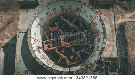 Aerial top view of abandoned and ruined Nuclear Power Plant. Large industrial construction with round tower of atomic reactor, post-apocalypse and world war concept, drone shot. stock photo