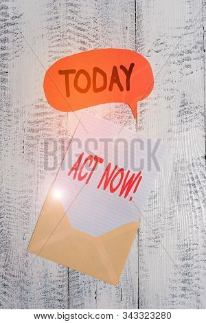 Text sign showing Act Now. Conceptual photo fulfil the function or serve the purpose of Take action Do something Front view open envelop speech bubble paper sheet lying wooden background. stock photo