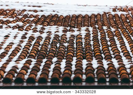 Tiled clay red roof in the snow. Medieval old roof in winter. Clay tiles in a row. Tiled background. Building structure stock photo