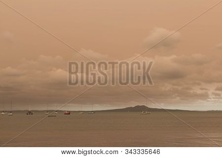 New Zealand, North Island - January 5 2020: the view of haze in the sky from Australia's bushfires hangs over Torbay Beach with Rangitoto island on background on January 5 2020, New Zealand. stock photo