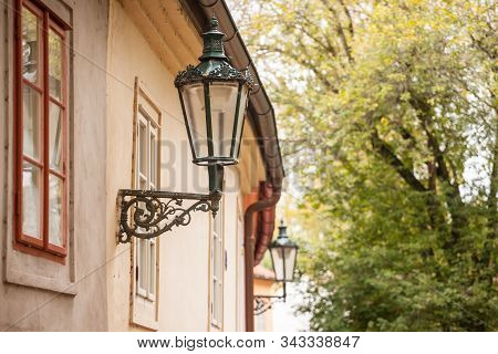 Vintage old public lamp, typical lantern from the 19th century, on Novy Svet Street, a picturesque medieval and narrow street of Hradcany hill in Prague, Czech Republic, with medieval houses. stock photo