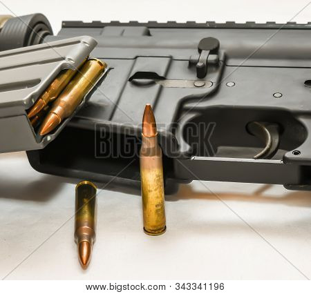 An multi colored AR 15 rifle with a rifle magazine loaded with 223 caliber bullets on it with two of the same bullets in front of it on a white background stock photo