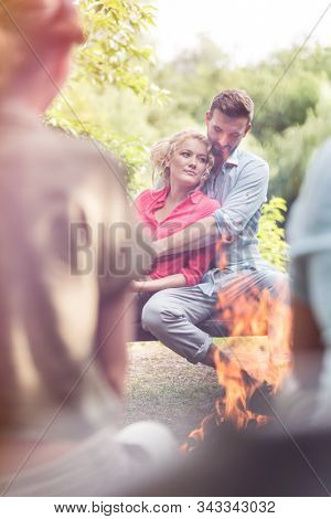 Young man embracing woman while sitting with friends at campsite in public park stock photo