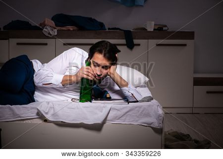 Young employee working at home after night shift stock photo
