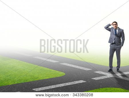 Young businessman at crossroads in uncertainty concept stock photo