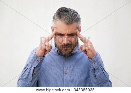 Extremely concentrated man touching temples and thinking hard. Grey haired young man in blue casual shirt posing isolated over white background. Thoughts or concentration concept stock photo