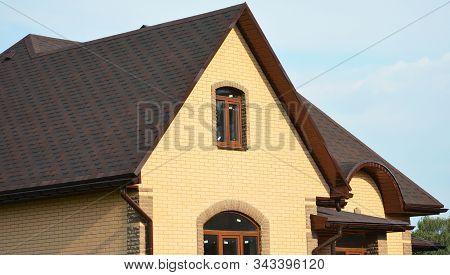 Asphalt shingles rooftop. Roofing construction rooftop house building with asphalt shingles, rain gutter and roof ventilation. Close up on asphalt roofing shingles. stock photo