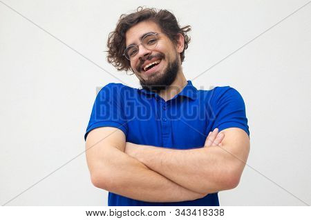 Positive carefree guy with folded arms shrugging shoulders, laughing. Handsome bearded young man in blue casual t-shirt posing isolated over white background. Carefree laughter concept stock photo