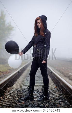 Lonely girl in black clothing standing between the rails in a fog. She holds a black and white balloon in her hands and loking at it. Concept of choice, good and evil stock photo