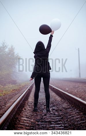 Lonely girl in black clothing stands back between the rails in a fog. She holds a black and white balloon in her hand and it fly away. Concept of choice, good and evil, way of life stock photo