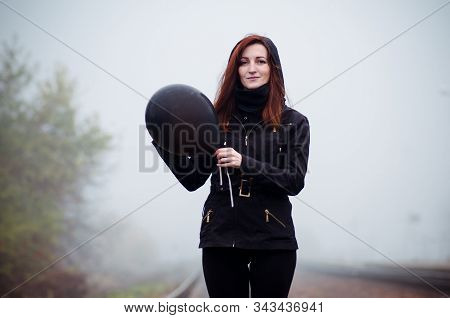Lonely girl in black clothing walking in a fog. She holds a black balloon in her hand. Concept of choice, target, good and evil, way in life stock photo