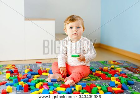 Adorable baby girl playing with educational toys . Happy healthy child having fun with colorful different wooden blocks at home in domestic room. Baby learning colors and forms stock photo