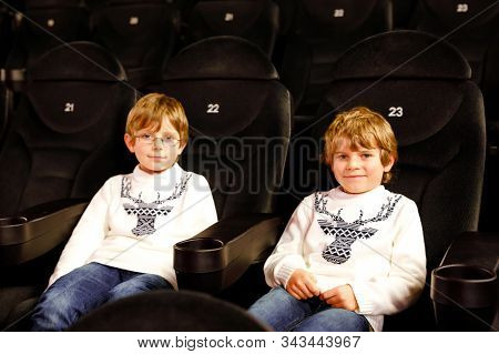 Two little adorable blonde kid boys waiting for a film at cinema. Siblings, twins and brothers having fun with activity of watching movies. Best friends on seats in dark room. stock photo