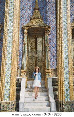 Beautiful charming tourist Asian woman in white dress with jean jacket standing on white stairs in front of beautiful door between pillars at Wat Phra Kaew The Grand palace stock photo
