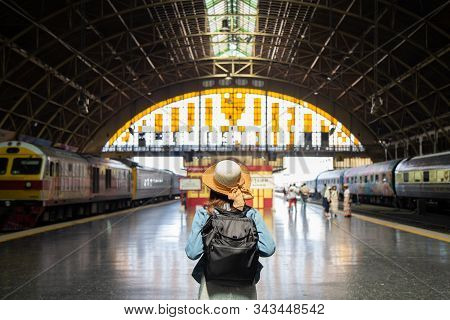 Beautiful charming tourist Asian woman in white dress with jean jacket with sweet straw hat carrying black backpack at train station, planning happy holiday vacation, This is The main train station build by goverment and public area. concept. stock photo