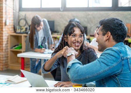 Candid of indian asian woman and man are fist bumping after finished work or project. Team Business Partners Giving Fist Bump to Greeting Start up project. Corporate Teamwork Partnership in Office. stock photo