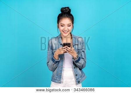 Portrait of Happy asian woman feeling happiness and standing typing smartphone on blue background. Cute asia girl smiling wearing casual jeans shirt and connect internet shopping online and surfing. stock photo
