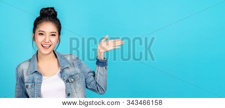 Banner of Happy asian woman feeling happiness and gesture hand open on blue background. Cute asia girl smiling wearing casual jeans shirt and present on copy space. stock photo