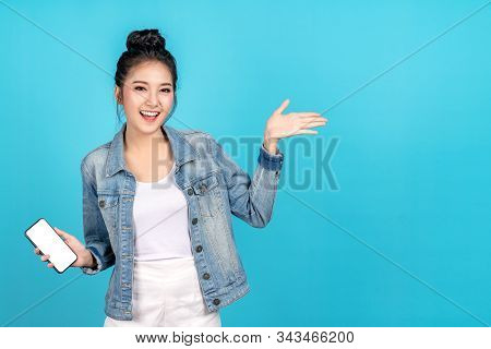 Happy asian woman feeling happiness and standing hold smartphone other hand open on blue background. Cute asia girl smiling wearing casual jeans shirt and connect internet shopping online and present stock photo