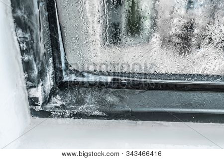 Winter home insulation window frost problem. Condensation on house and apartment windows causing ice forming on the interior. stock photo