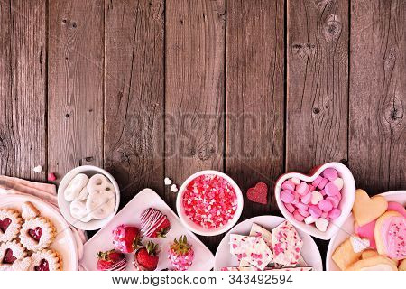Valentines Day bottom border of assorted sweets and cookies. Above view over a wooden background. Love and hearts theme. Copy space. stock photo