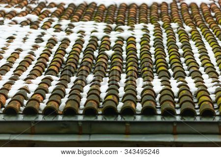Tiled clay red roof with green moss in the snow. Medieval old roof in winter. Clay tiles in a row. Tiled background. Building structure stock photo
