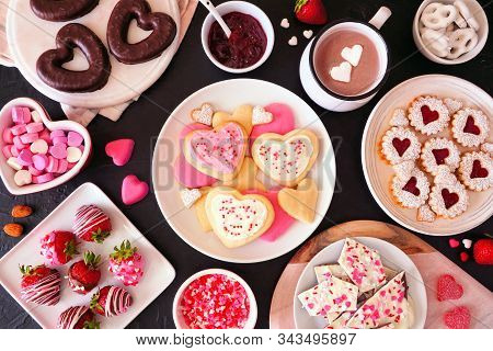 Valentines Day table scene with assorted sweets and cookies. Above view over a dark background. Love and hearts theme. stock photo
