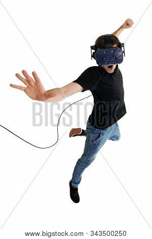 Screeming young man isolated on white background playing game in virtual reality glasses. Virtual reality simulator. inovate intertainment technology stock photo